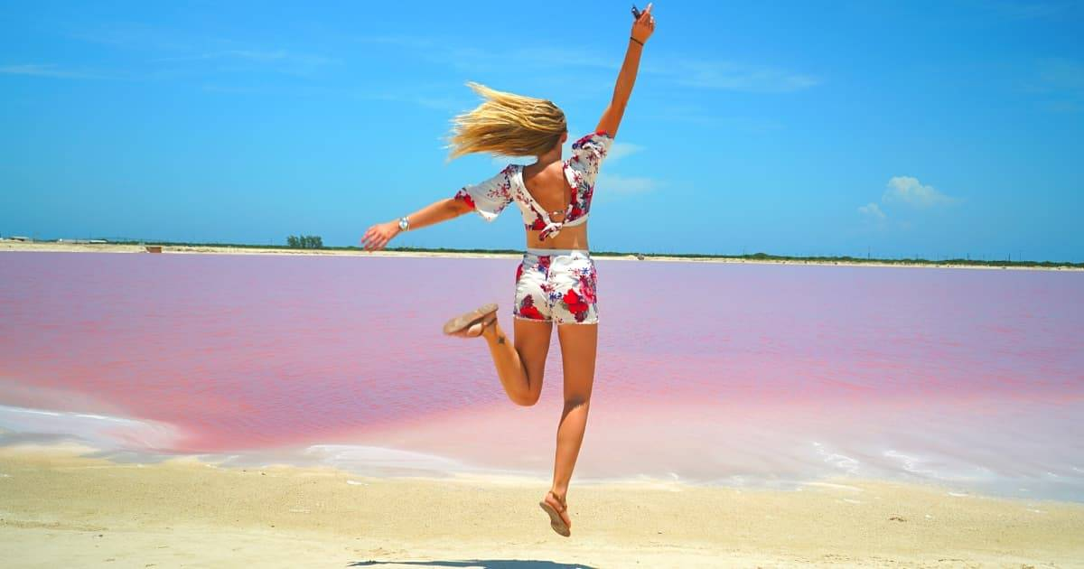 Woman jumping at Las Coloradas pink lakes in the Yucatan Peninsula of Mexico | first time solo travel destinations