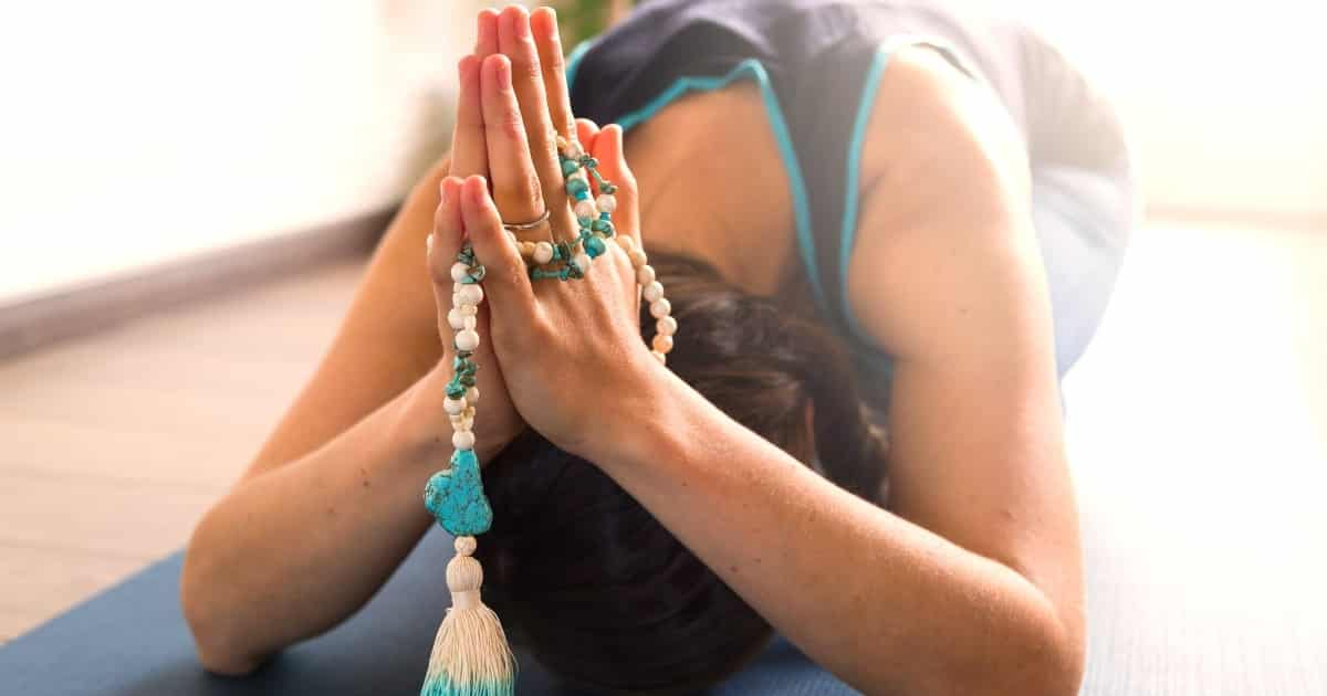 Woman with prayer hands and mala beads on a yoga mat