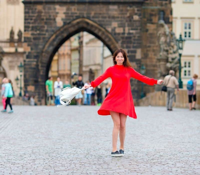 Woman in a red dress twirling in the street