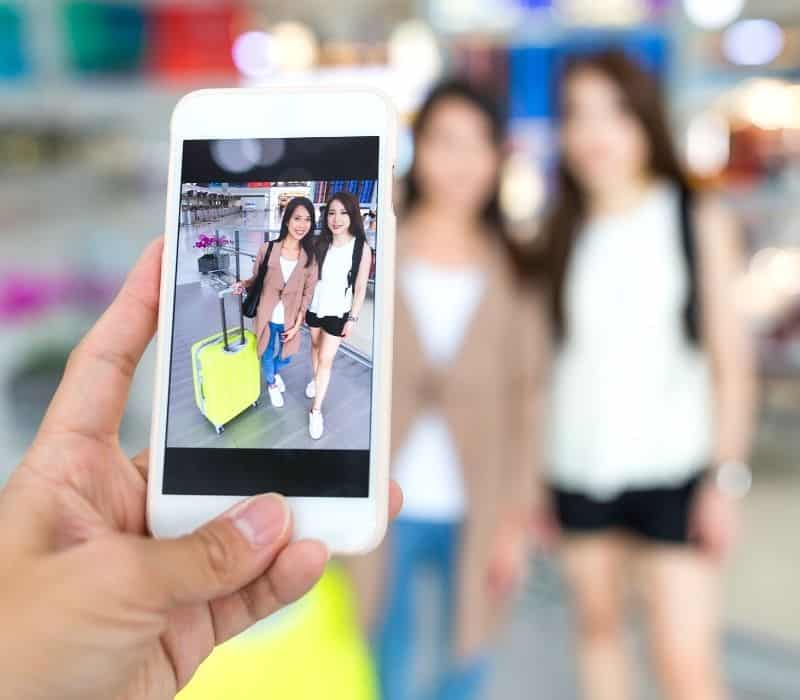woman taking a photo of two other women at the airport | solo travel photography