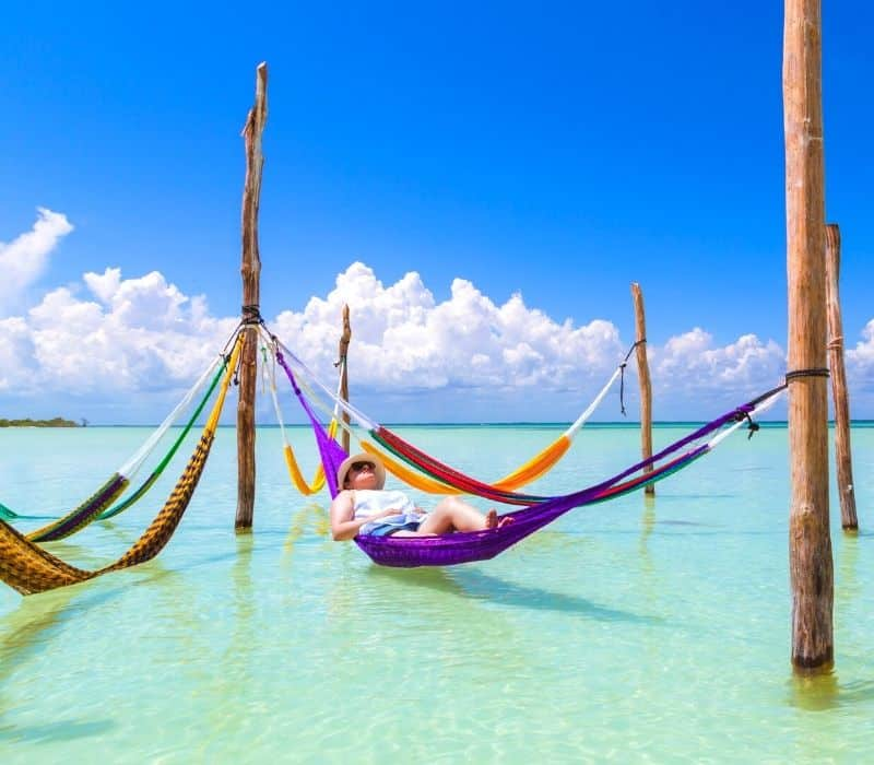 woman laying in the Caribbean Sea on a hammock in Holbox Island, Mexico
