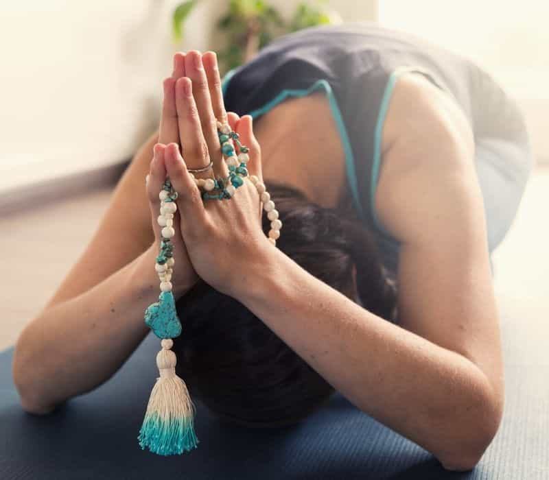 woman on her yoga mat with prayer hands and meditation beads