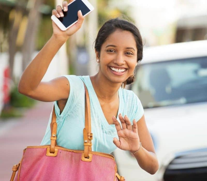 Woman standing in the street holding her phone waiting for an Uber