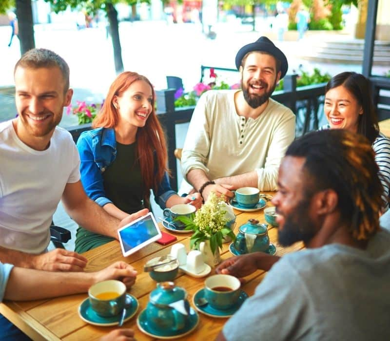 Group of friends at a cafe | Solo travel anxiety