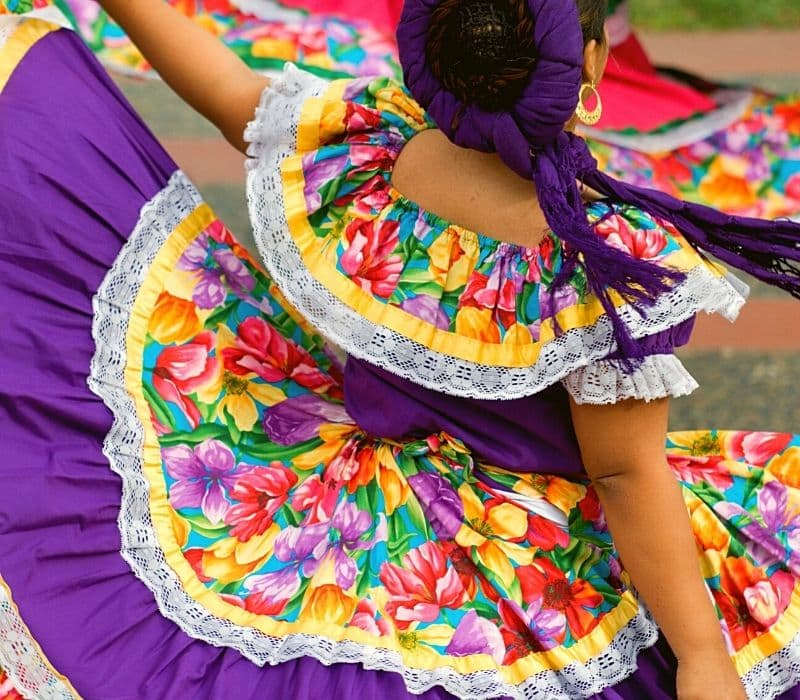 Woman in traditional Mexican dress doing a dance