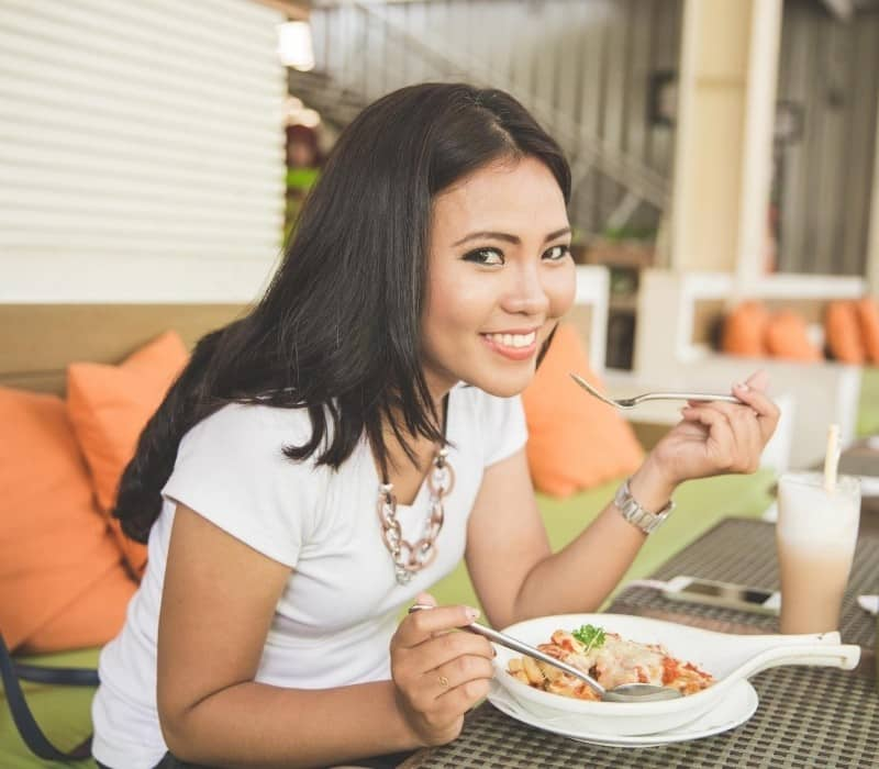 Happy woman eating alone at a restaurant