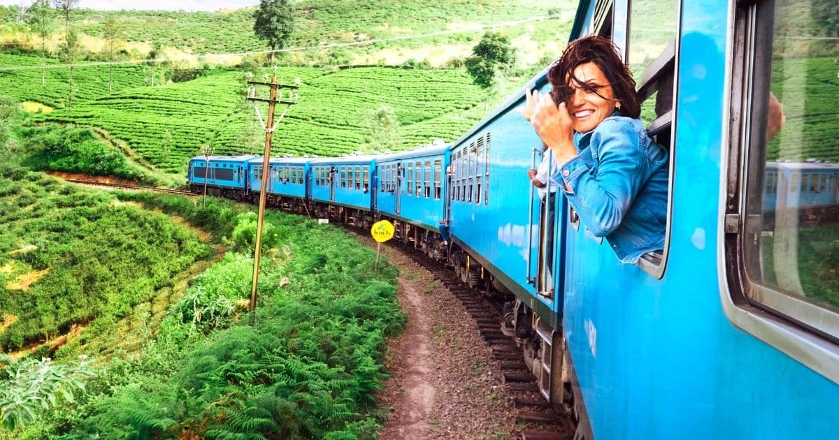Happy young woman with with her head sticking out the window of a blue train