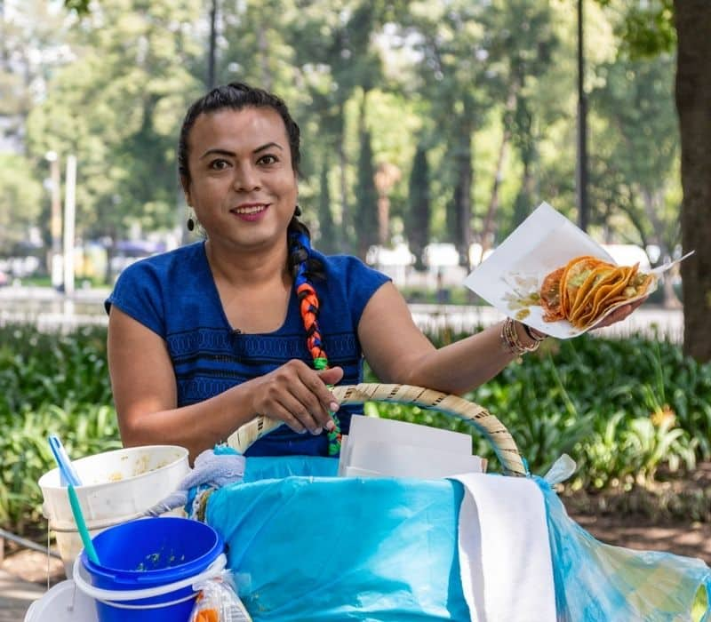 woman holding tacos to serve