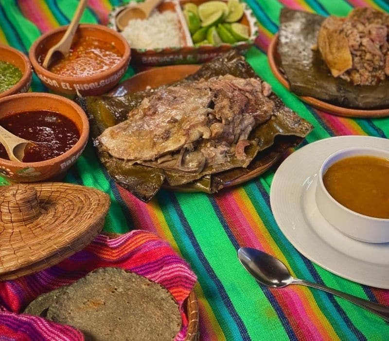 table spread of tacos with limes, salsas, soup