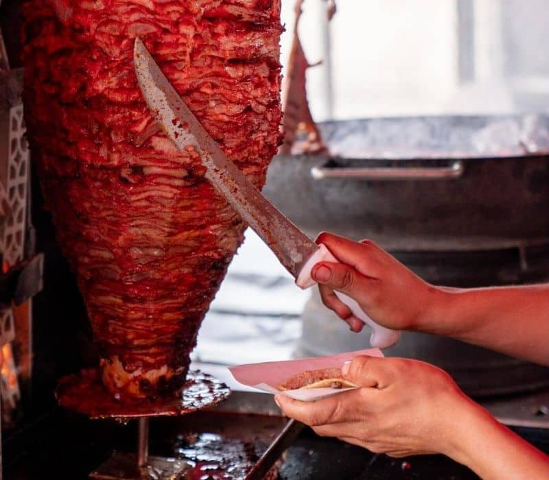 Cutting taco al pastor meat for a taco