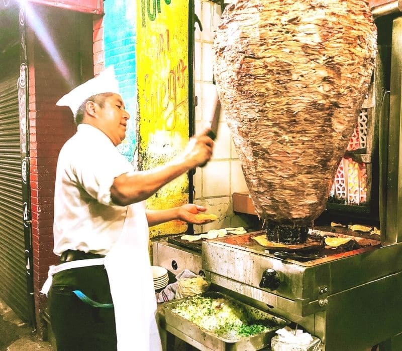 man cutting meat for a taco al pastor in mexico
