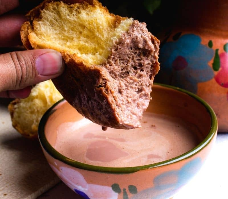 dunking a piece of bread into a cup of hot chocolate