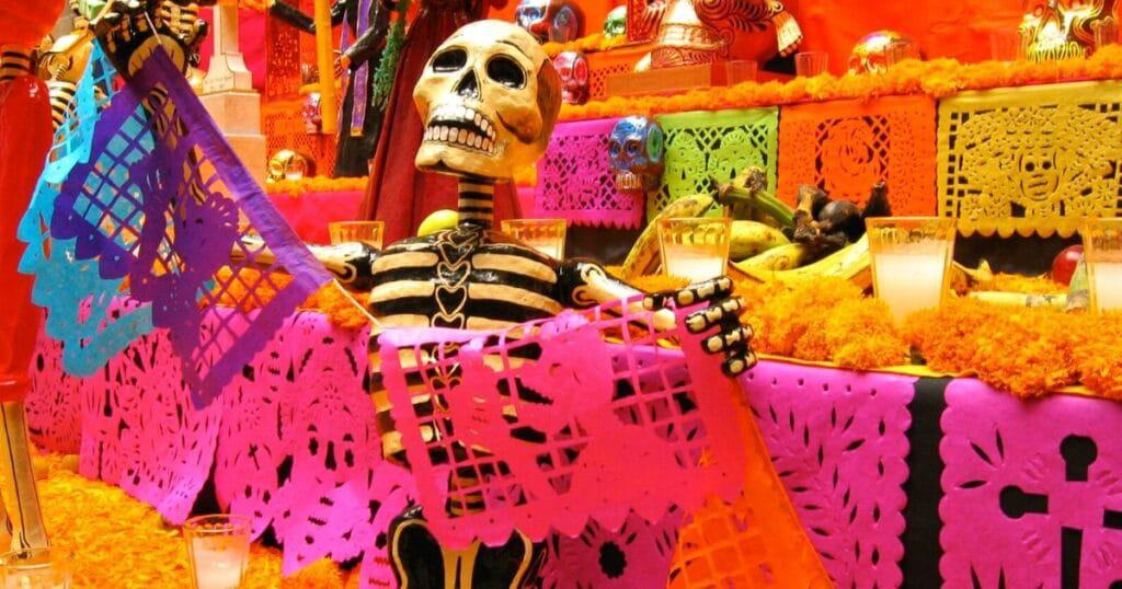 skeleton holding colorful flags on a colorful altar | oaxaca day of the dead in mexico