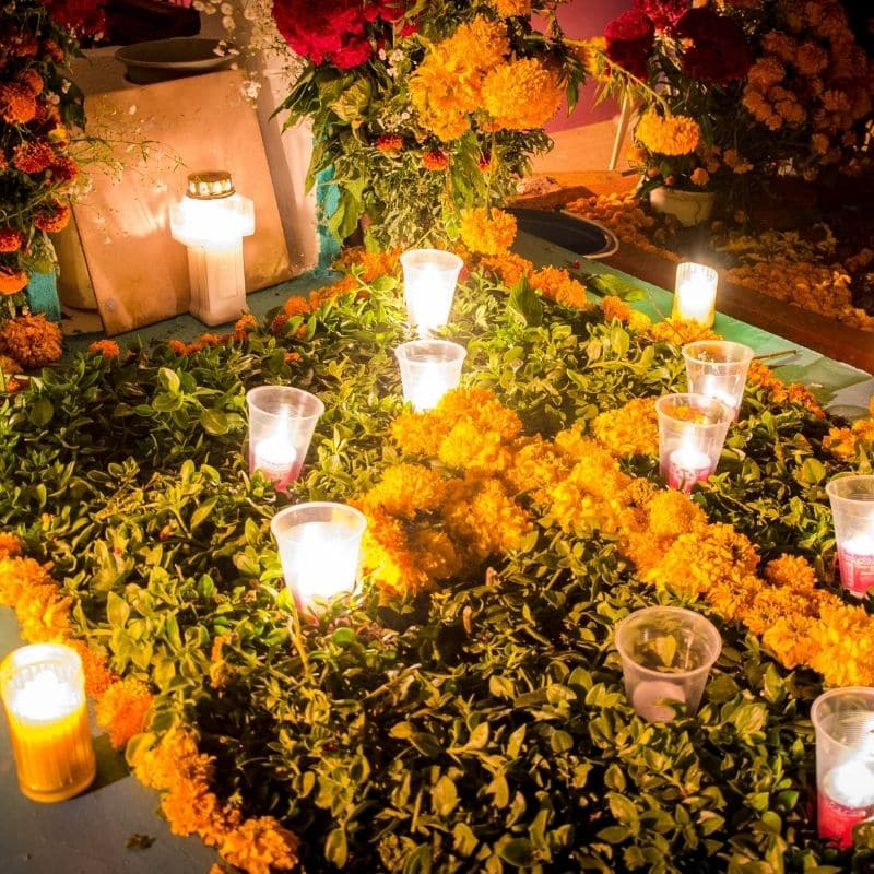 Day of the Dead cemetary with flowers and lit candles