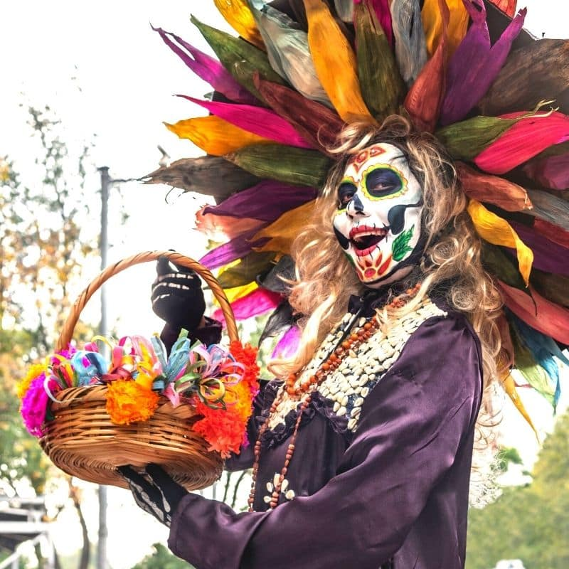 woman with her face painted to look like a skeleton for oaxaca day of the dead festival in mexico