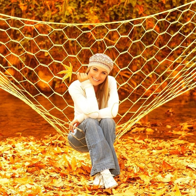 Happy woman on a hammock in fall foliage | Solo travel anxiety