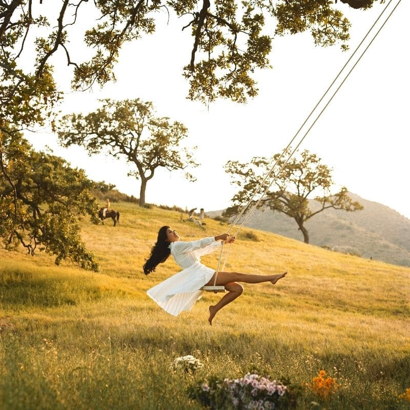 Happy woman on a swing in a mountain field | Solo travel anxiety
