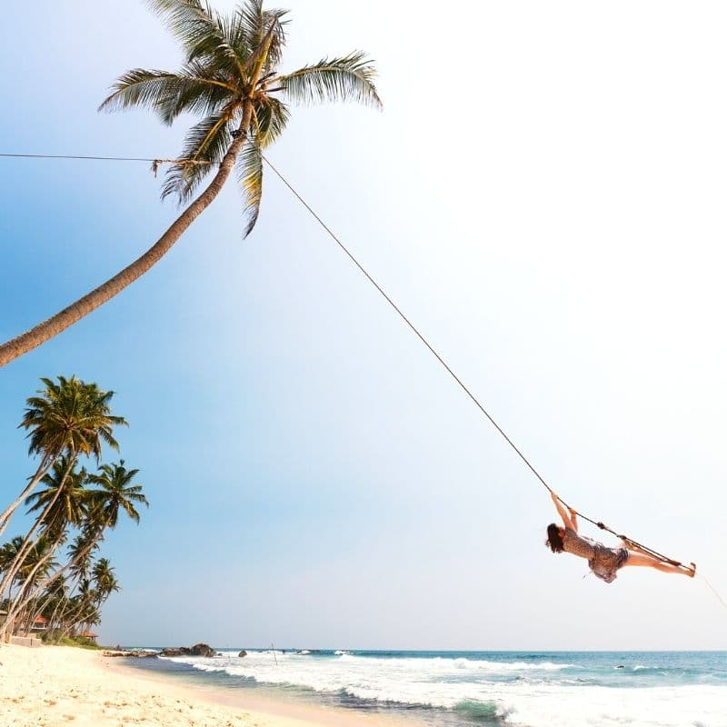 Happy woman on a beach tree swing | Overcome Solo Travel Anxiety