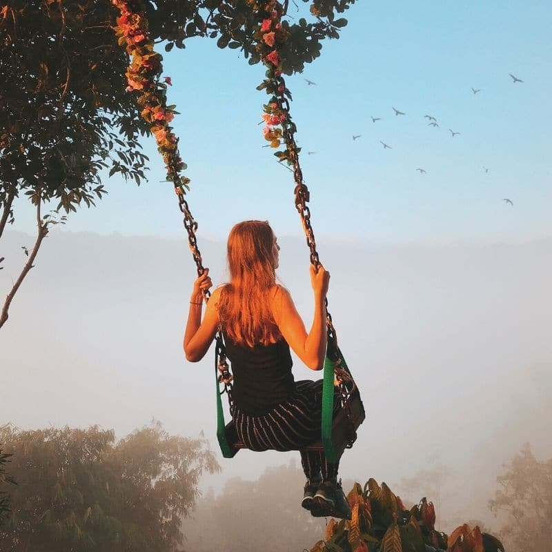Happy woman on a swing | Solo travel anxiety