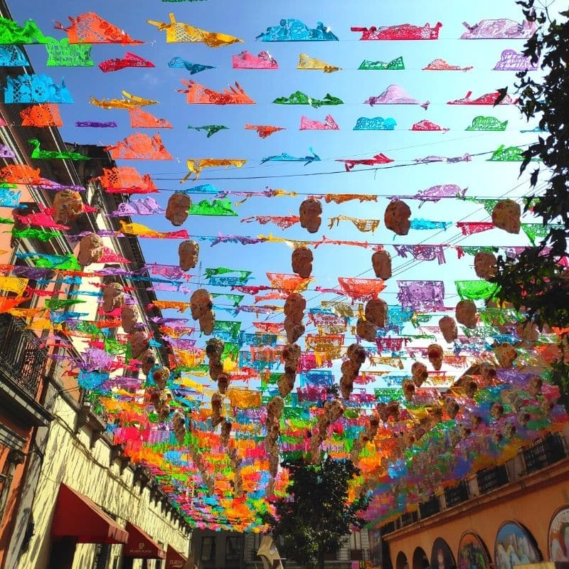 colorful flags hung across from one side of the stree to the other in oaxaca city | day of the dead mexico
