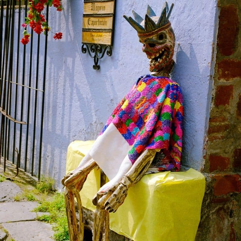 human skeleton wearing traditional mexican poncho and crown sitting on a yellow bench | oaxaca day of the dead in mexico
