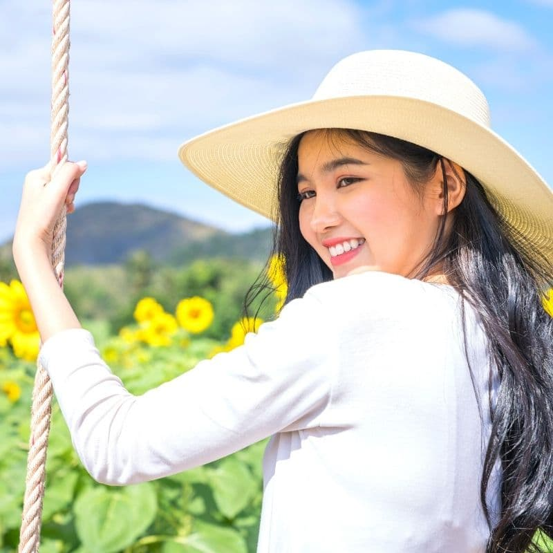 Happy woman on a swing in a sunflower field | Solo travel anxiety