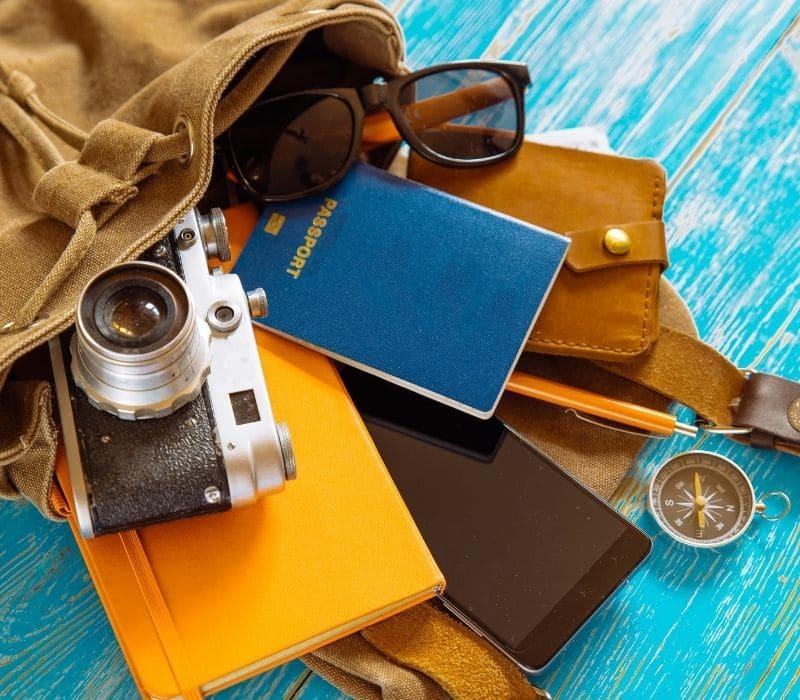 bag with passport, compass, wallet, sunglasses, passport falling out