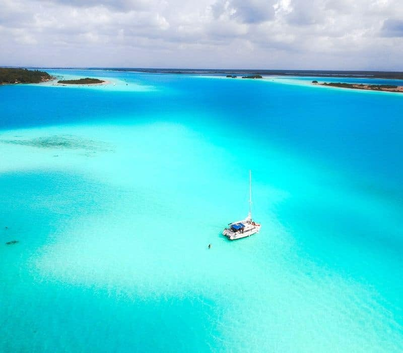 a sail boat in the middle of the blue waters of bacalar lagoon mexico