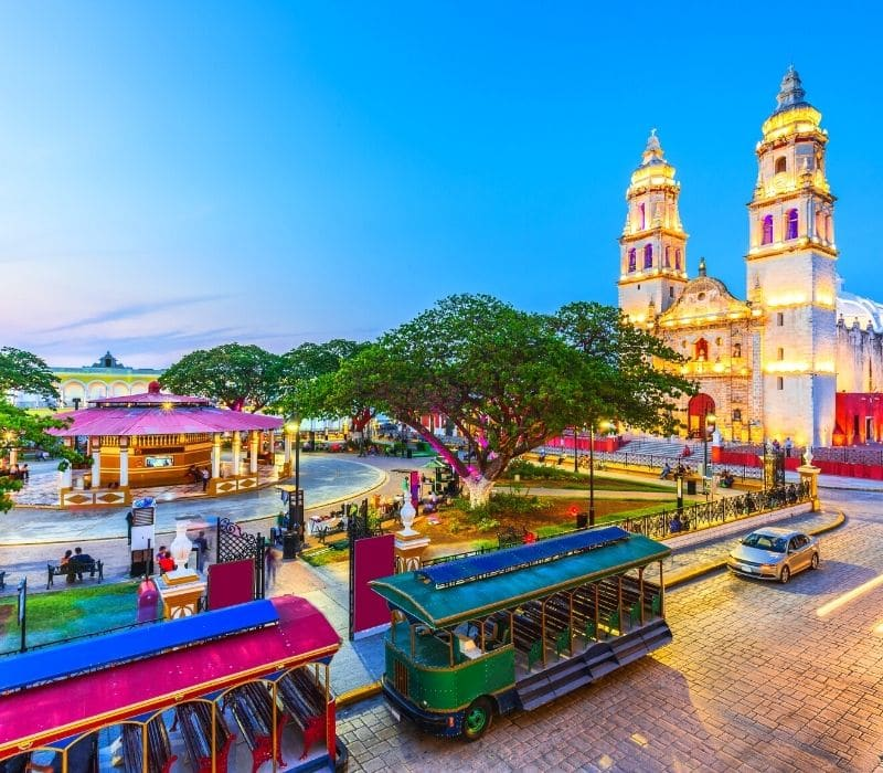 larger church, city tram and zocalo park in downtown Campeche City, Mexico