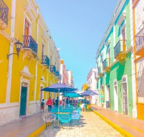 outdoors tables with umbrellas for shade at cafes in colorful downtown campeche city mexico on a merida day trip