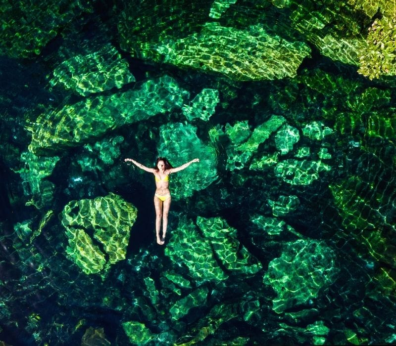 Woman floating in a cenote in Tulum
