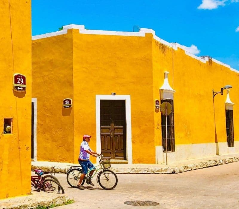 colonial town with yellow walls and man on his bike in the street in Izamal, near Merida, Mexico, Yucatan Peninsula