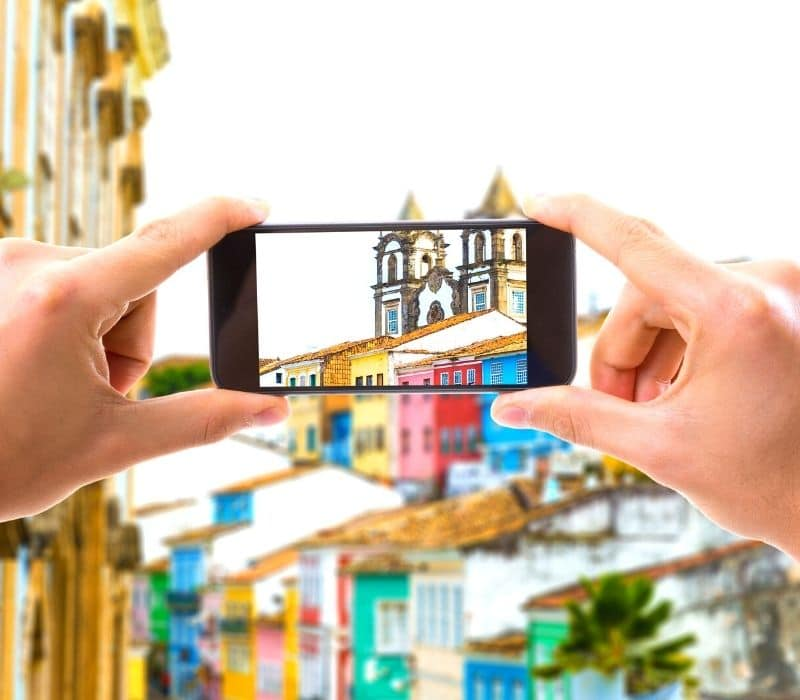 hands holding an iphone and taking a photo of a colorful old town | solo travel photography