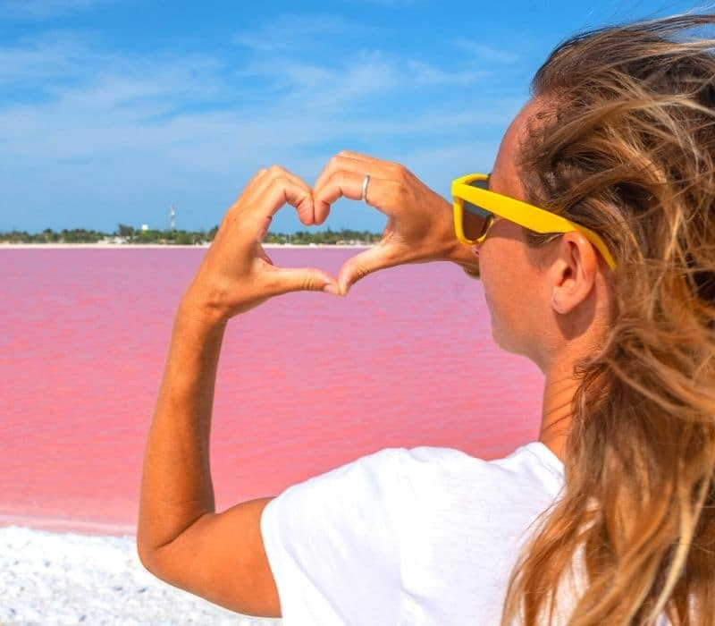woman making a heart shape with her two hands at the pink lakes of Las Coloradas, near Merida, Mexico, Yucatan Peninsula
