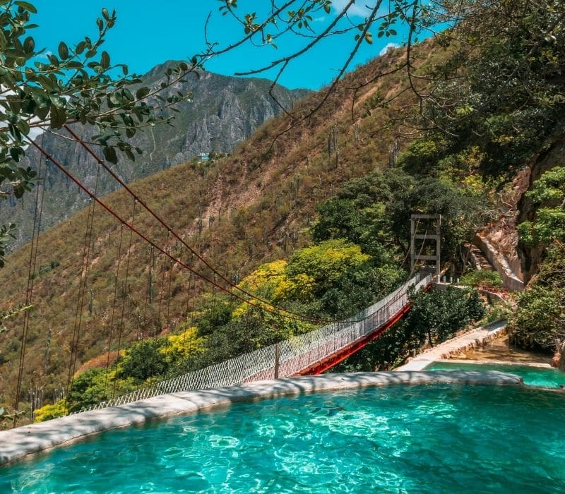 blue water pools with a bridge in the background - Visit Las Grutas Tolantongo