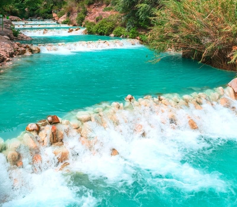 blue river water cascading over rocks - Visit Las Grutas Tolantongo