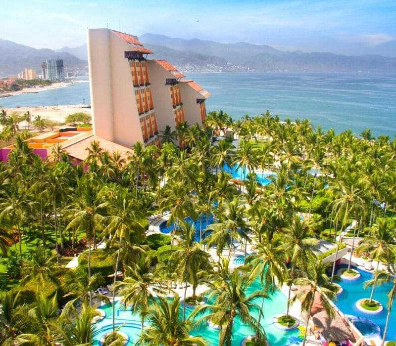 large all inclusive resort hotel on the beach with elaborate pool area surrounded by palm trees | things to do in puerto vallarta mexico