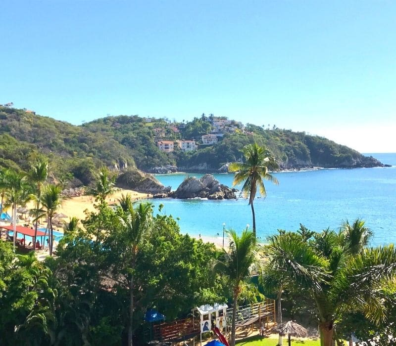 beautiful blue water in a bay and beach cove in the small beach town of Bahias de Huatulco, Mexico, in Oaxaca state, a safe solo Mexico travel destination in southern Mexico on the Pacific Ocean