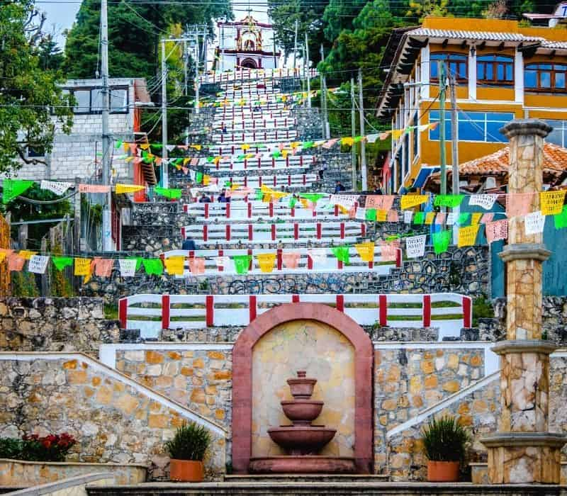 Colorful Mexican folk art flags (papel picado) on a street in San Cristobal de las Casas pueblo magico (magic town), a great place for Solo Mexico travel in Chiapas, Mexico,