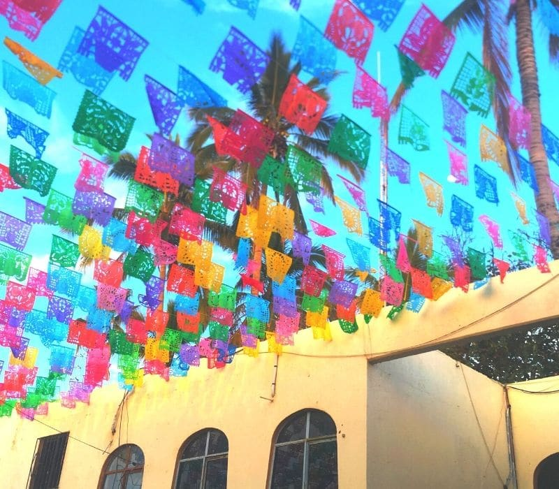 Colorful Mexican folk art flags (papel picado) on a street in Todos Santos pueblo magico (magic town), a great place for Solo Mexico travel in Baja California, Mexico,