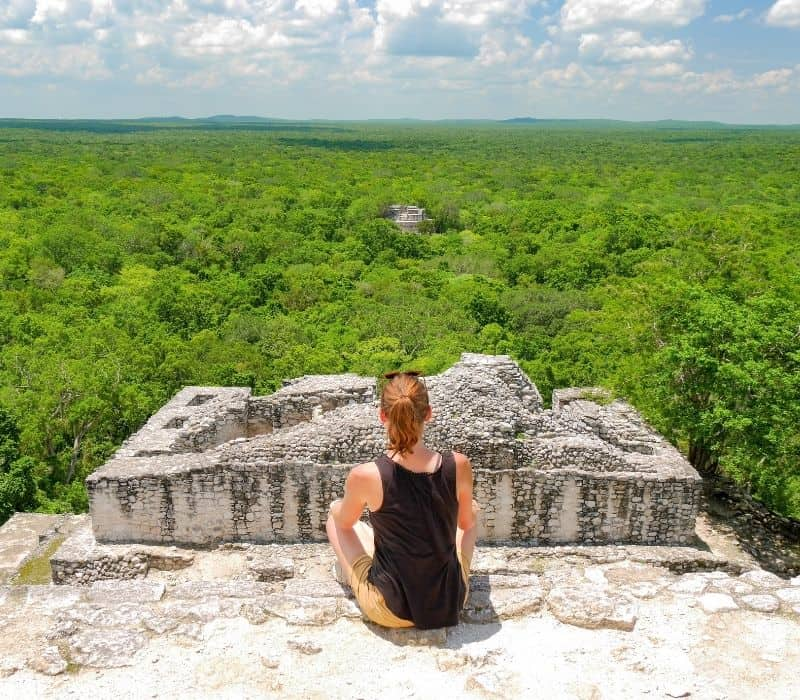 woman in a black tank top sitting on top of mayan pyramid in the jungles of mexico, Calakmul ruins, one of the most unique places to visit in mexico