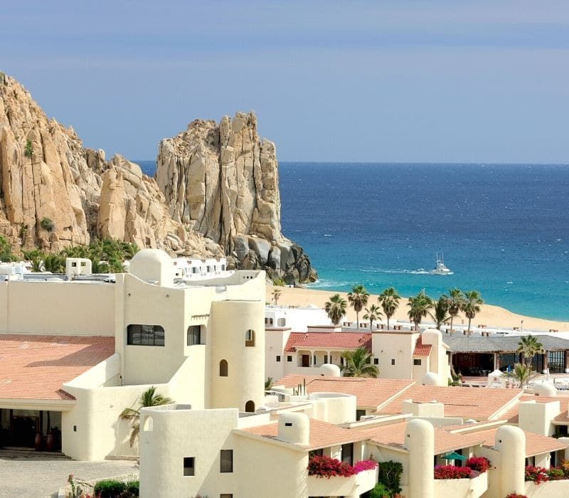 beautiful white homes with pink roofs and large white rock formations behind on the beach in cabo san lucas, one of the Best Mexican Beach Towns