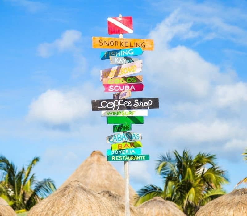 colofrul beachside signs and huts with thatched palapa roofs on the beach in Cozumel, one of the Best Mexican Beach Towns