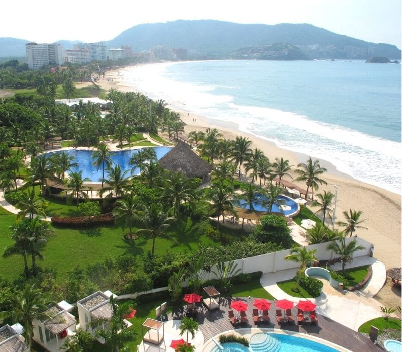 nice resorts with pools and beach chairs and green palm tree landscape on the pacific ocean with mountains in the background in Ixtapa, one of the Best Mexican Beach Towns