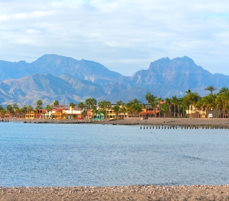 colorful homes on the water and mountains in the background in beautiful loreto, one of the Best Mexican Beach Towns