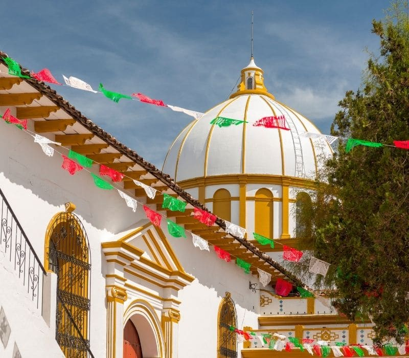 white dome church with gold trim on the dome and building of this colonial church with red, white and green flags (bunting, streamers) hung from this building in san cristobal de las casas, , one of the most unique places to visit in mexico