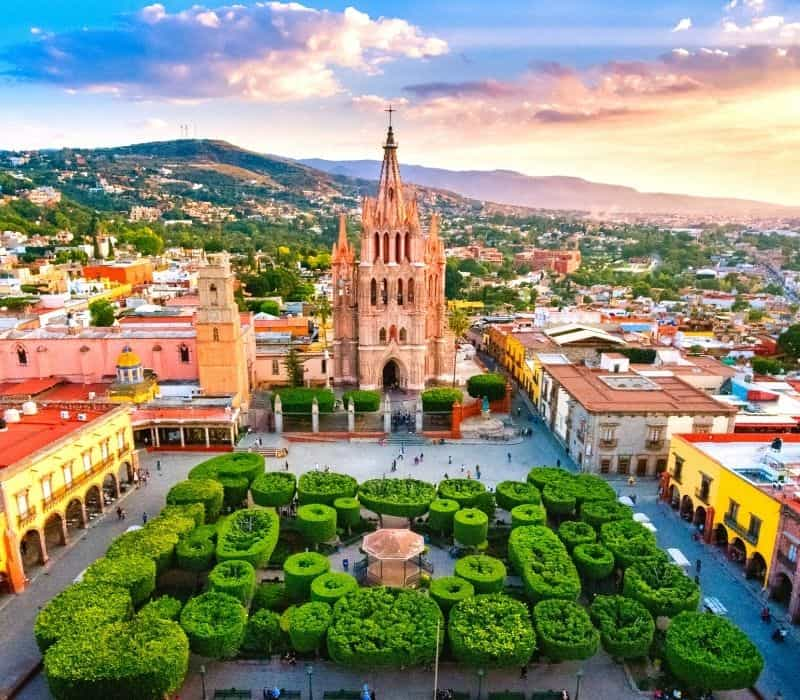 large pink gothic style church in san miguel de allende mexico in front of a well manicured park/garden with trees cut into topiary style circles and colorful buildings in colonial architecture styles surrounding the town square