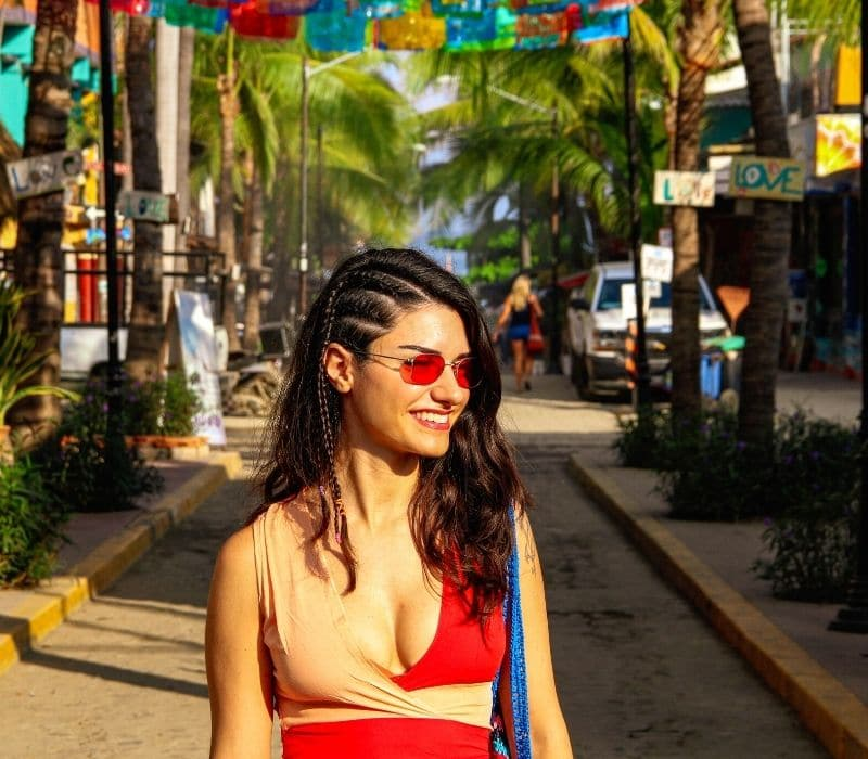 woman smiling on a colorful street in Sayulita, one of the Best Mexican Beach Towns