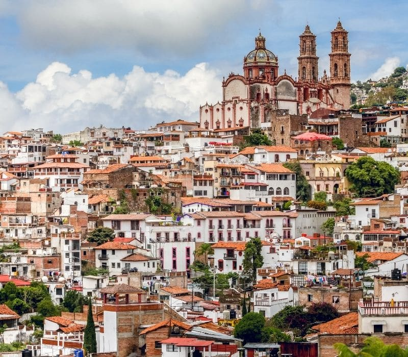 the white and tan building of the mountain town of Taxco , one of the most unique places to visit in mexico