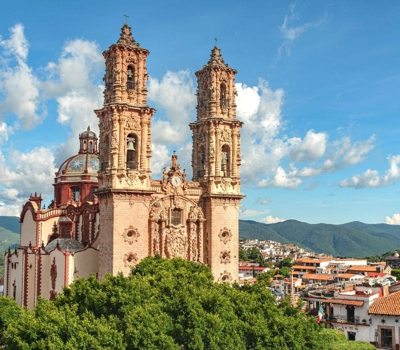 large tan church with colorful dome in the ornate baroque style site high atop the town of taxco, one of the most unique places to visit in mexico